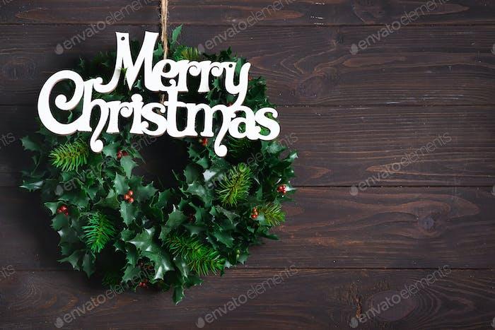 Weihnachtsdekoration Kranz von grünen Blättern und Beeren Stechpalme Ilex Pflanze mit Brief Frohe Weihnachten