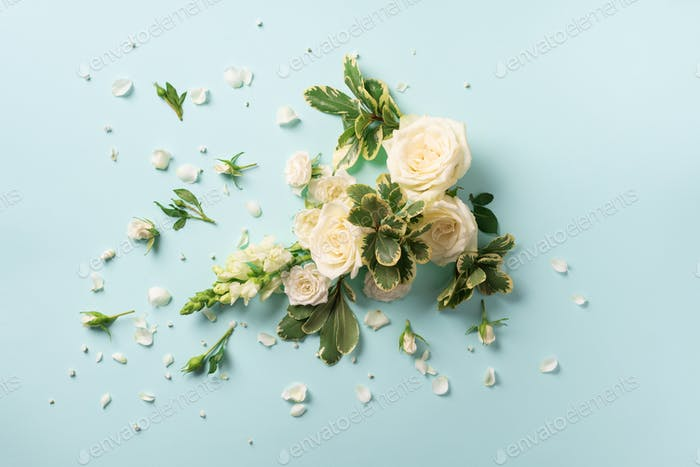 White roses, lily, gerbera over blue background. Flat lay, top view. Creative layout. Spring or