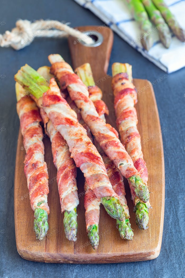 Healthy appetizer, green asparagus wrapped with bacon on board,