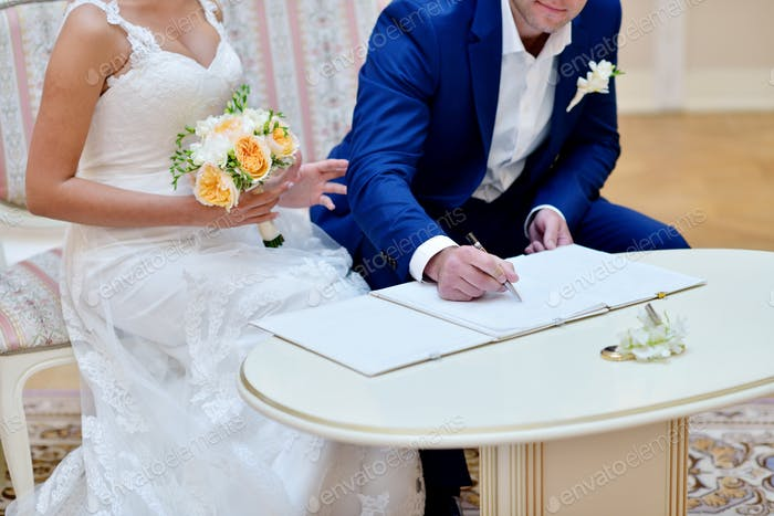 Beauty bride and handsome groom are registering the marriage