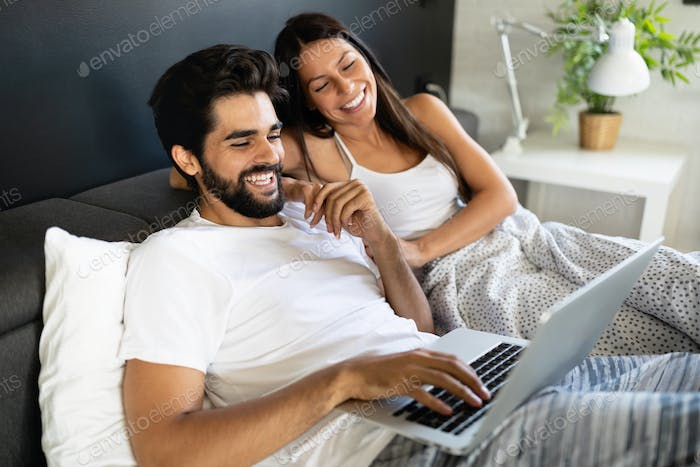 Cheerful couple shopping online lying on their bed