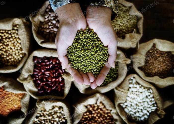 Variety of seeds products on the sack and hands with mung bean
