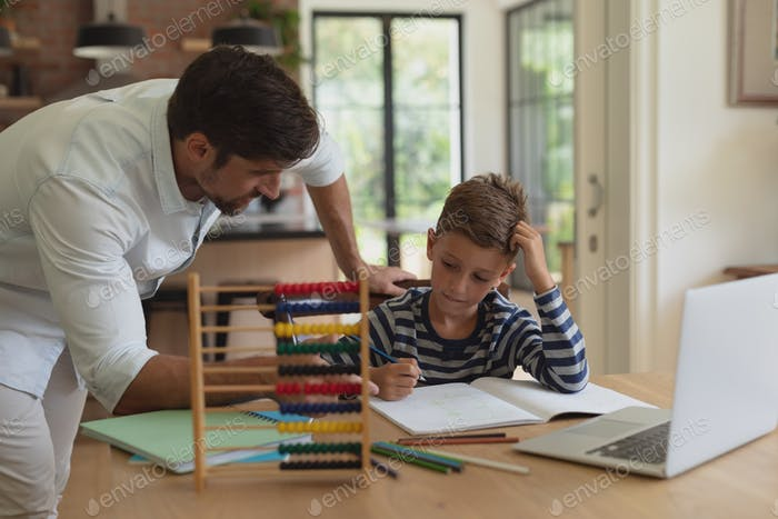 Front view of Caucasian father helping his son with homework in a comfortable home