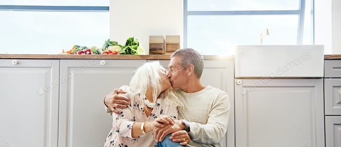 Elderly couple kissing on a kitchen floor