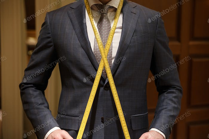 Cropped image of man with measuring tape on neck