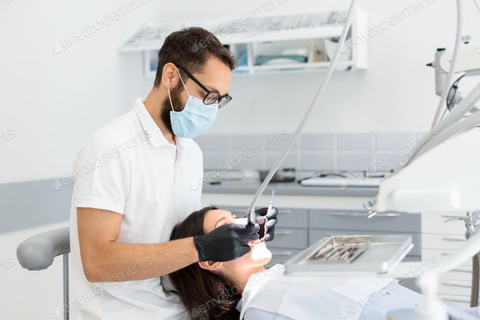 Dentist doctor in glasses filling teeth to female patient