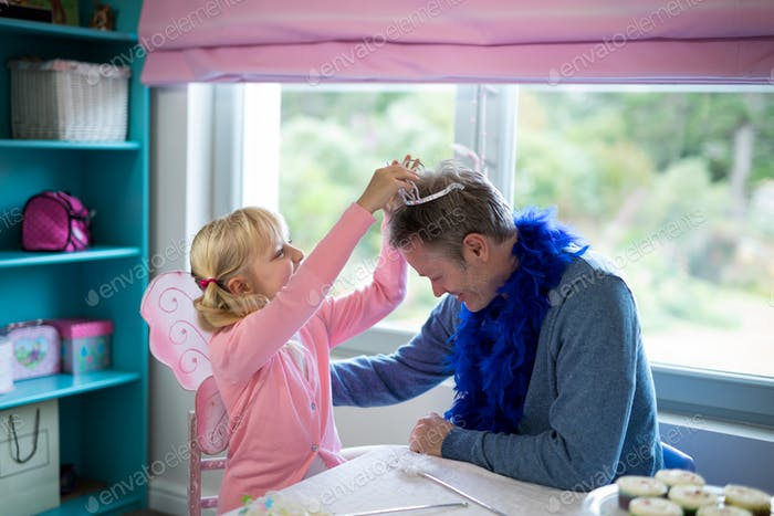 Girl pretending to be a fairy playing with her father