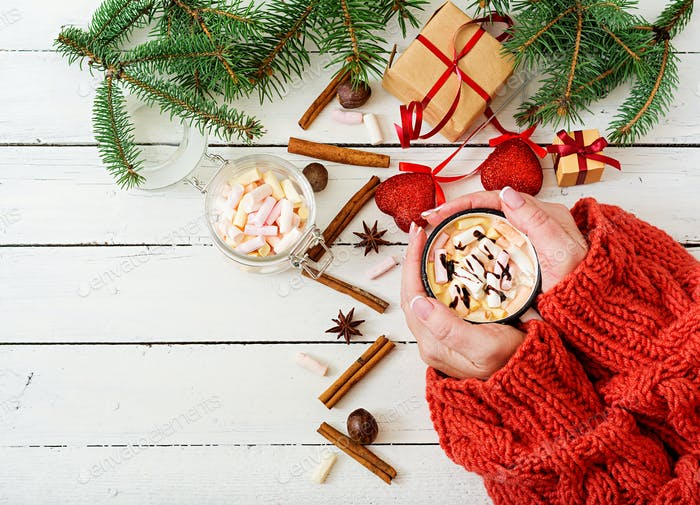 Female hand holding a cup of hot cocoa or chocolate with marshmallow
