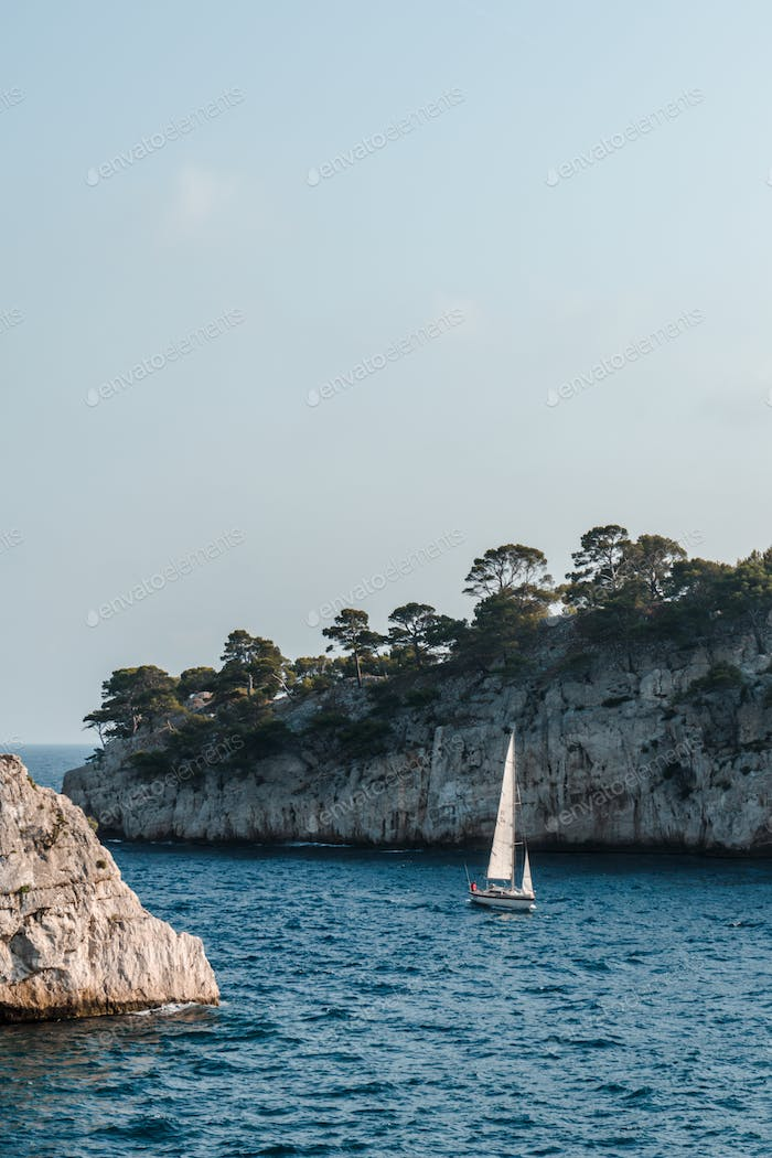 Sailboat on waves against the background of rocks