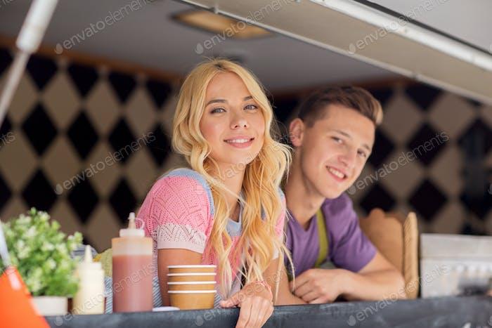 счастливые молодые продавцы в продовольственном грузовике