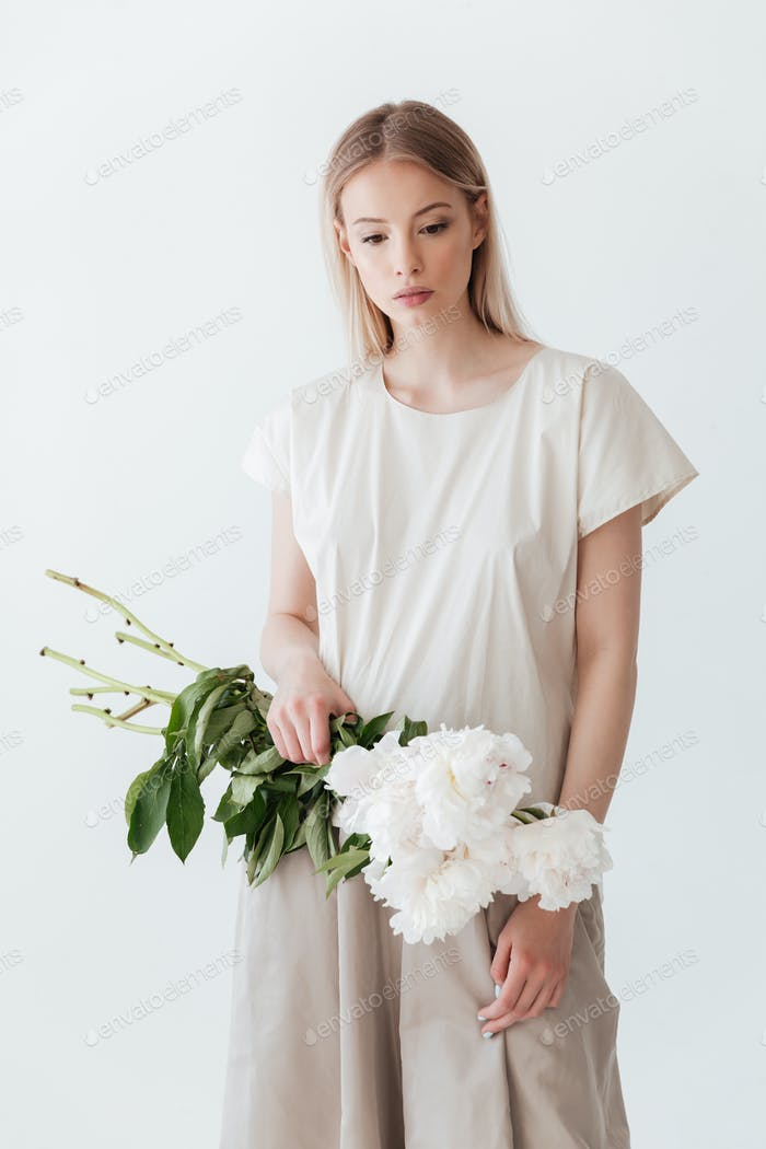 Blonde woman standing isolated holding flowers