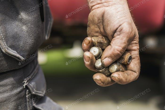 Männliche Hand hält fettige Autoteile