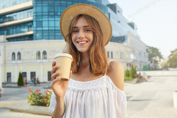woman wears stylish hat, feels happy, standing and drinking