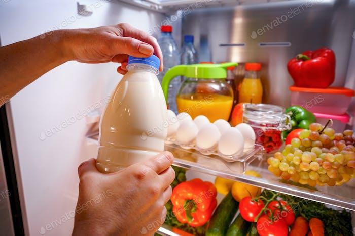 Frau nimmt die Milch aus dem offenen Kühlschrank