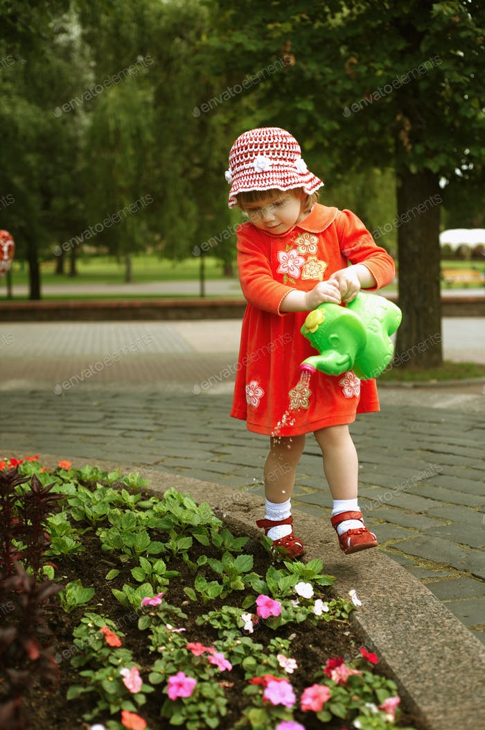 Cute girl watering flowers in the garden