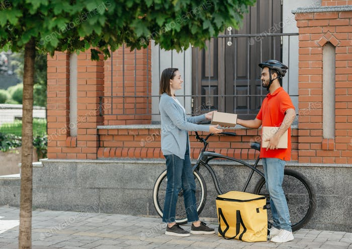 Buying in online store and delivery by courier. Smiling girl receives parcel from deliveryman with