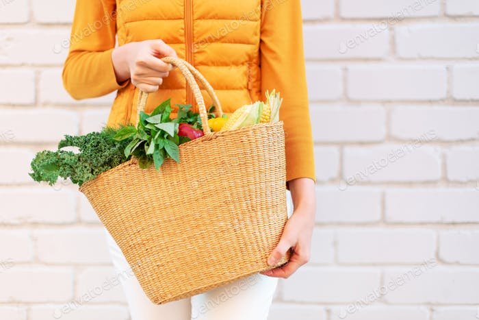 Young girl holding straw basket with vegetables, products without plastic bags, brick background
