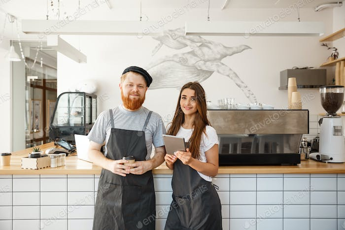 Coffee Business Concept - happy young bartender baristas ready to give service at modern coffee shop