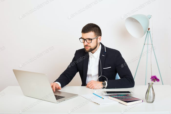 young handsome stylish hipster man in black jacket working at office table, business style