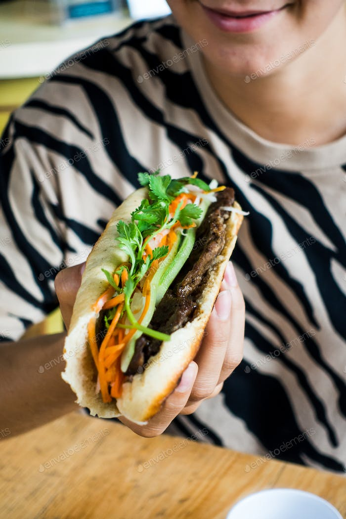 Girl eating Vietnamese baguette Banh Mi with fresh vegetables and grilled pork