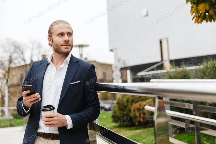 Image of young businessman holding coffee cup and cellphone on city street