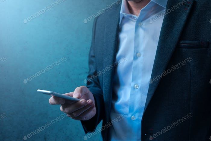 Handsome businessman in modern business suit using mobile phone