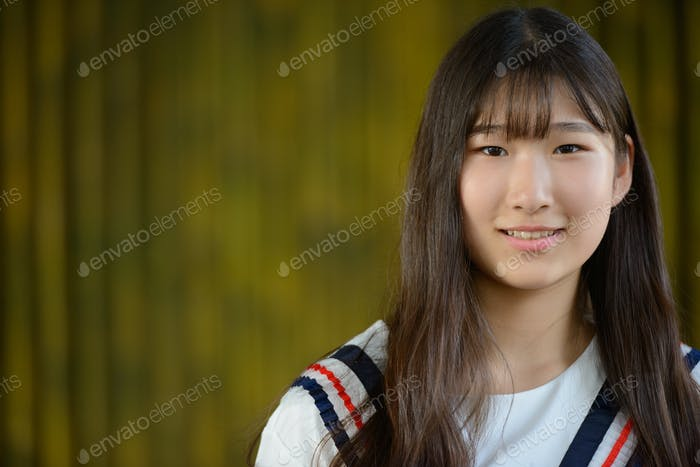 Happy young beautiful Asian teenage girl against bamboo fence