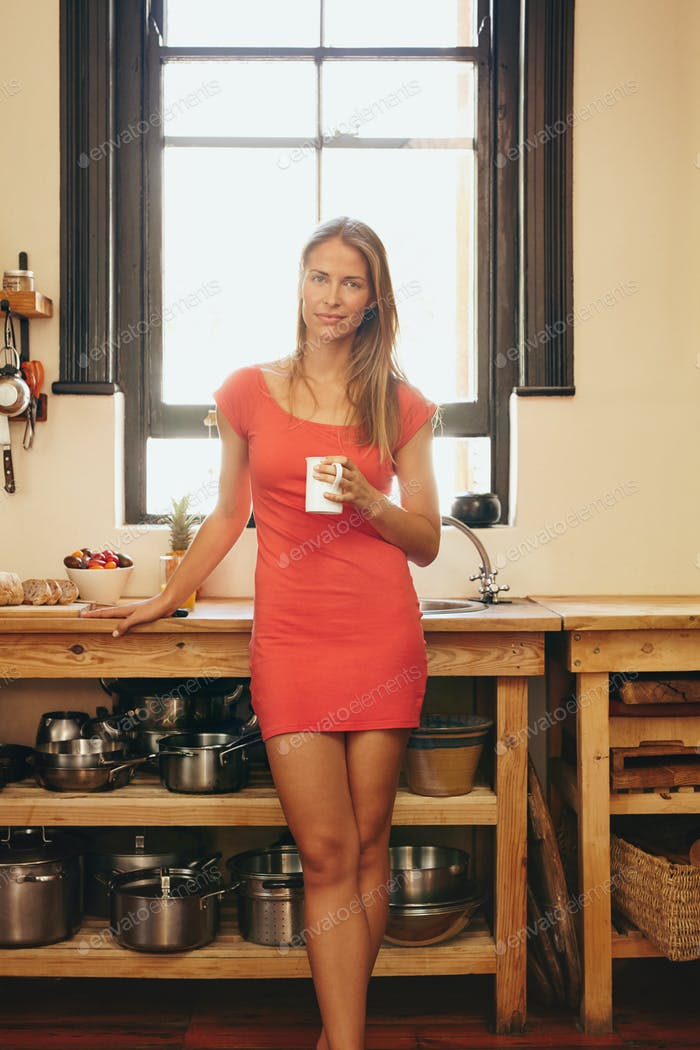 Attractive young woman in kitchen with a cup of coffee
