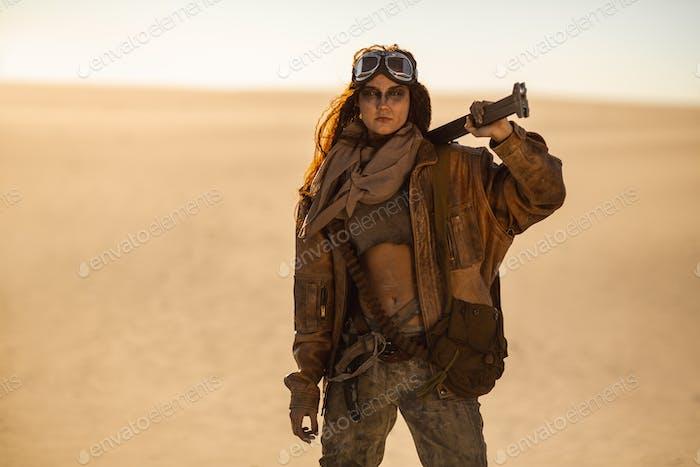 Bewaffnete postapokalyptische Frau im Freien in einem Ödland