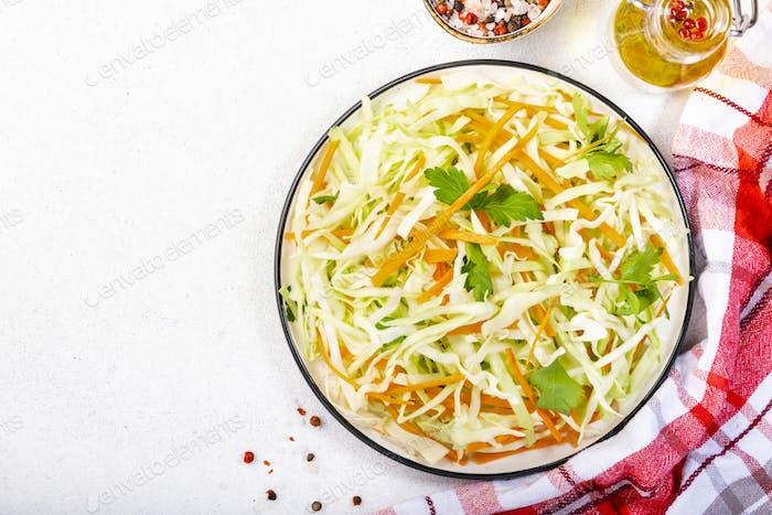 Weißkohl Salat Krautsalat mit Karotte auf weißem Küchentisch