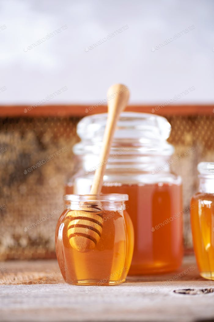 Honey products background. Honeycomb frame, bee pollen granules, honey in glass pot, almond nuts on