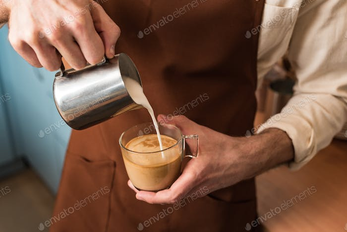 Cropped view of barista pouring milk in coffee