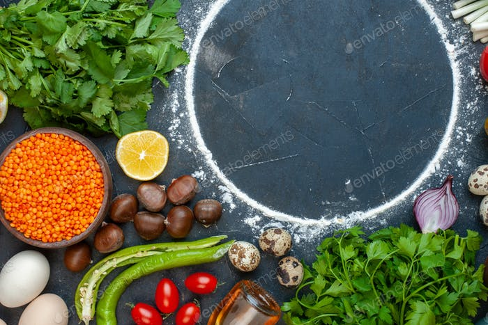 Horizontal view of meal cooking with eggs fresh vegetables spices eggs fallen oil bottle green