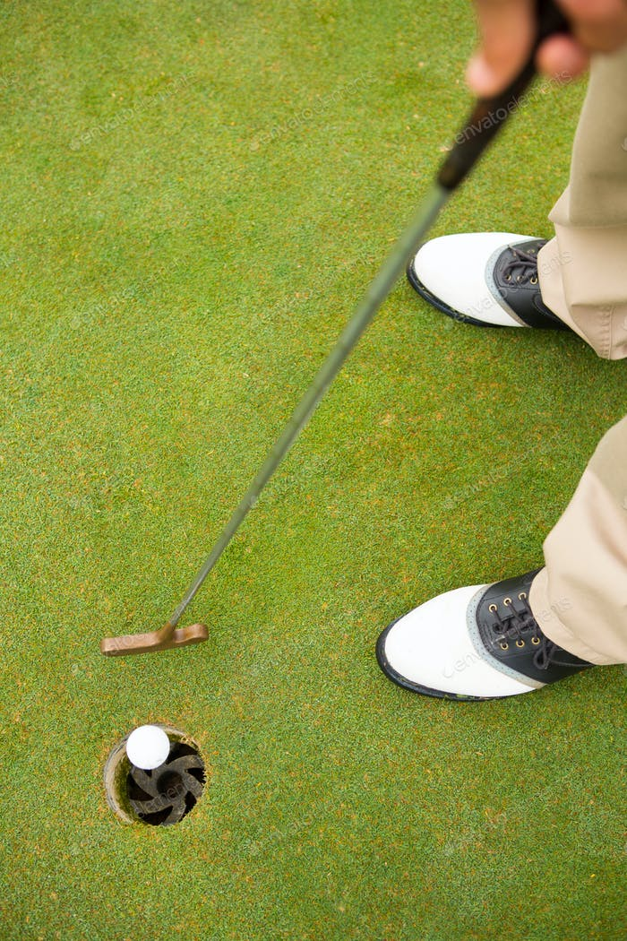 Golfer putting golf ball in the hole at golf course