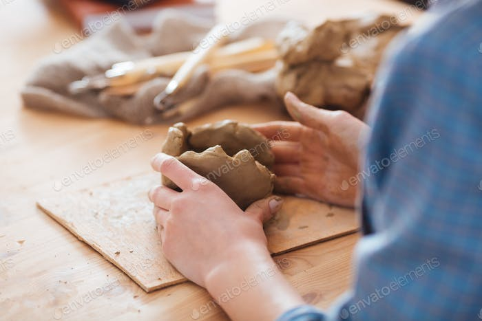 Woman ceramist hands working on sculpture at wooden table