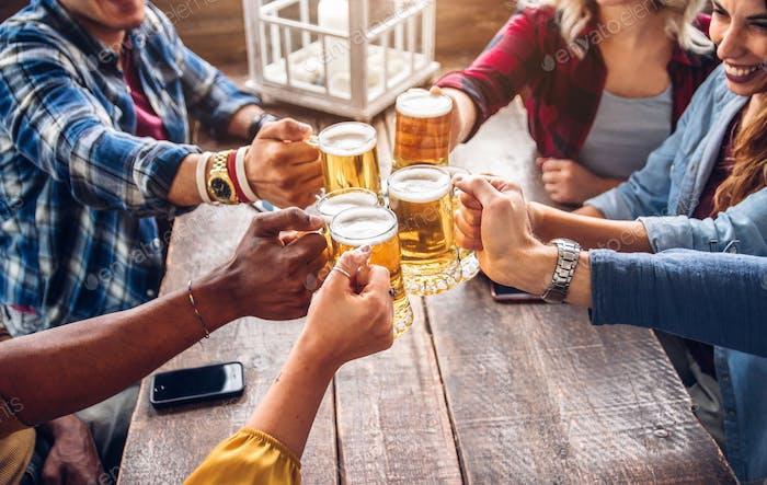Grupo de personas disfrutando y tostando una cerveza en el pub cervecero