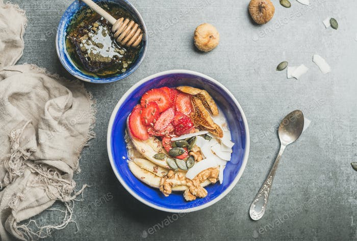 Yogurt, granola, seeds, berry and honey in blue ceramic bowl