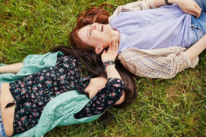 Zwei fröhliche Schwestern auf dem Gras liegend