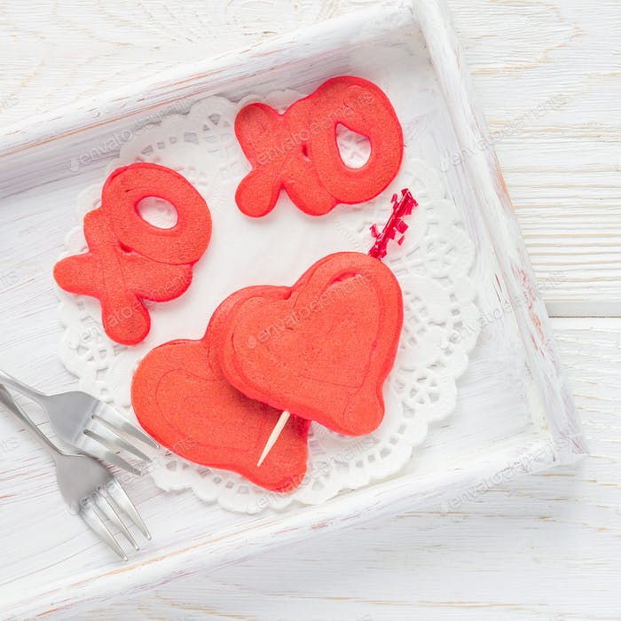 Red velvet pancakes with xo sign, hugs and kisses, and heart on wooden tray, top view, square format