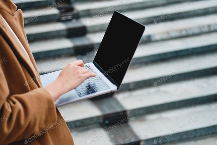 Close up stylish businesswoman working on laptop outdoor