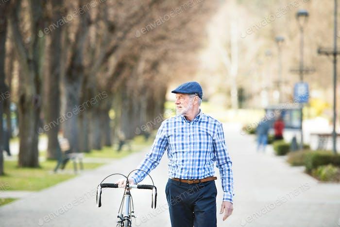 Senior Mann in blau kariertes Hemd mit Fahrrad in der Stadt.