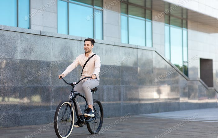 Modern generation and healthy lifestyle. Young businessman going to work by bike