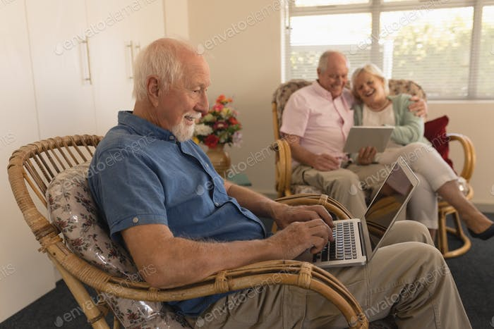 Senior man using laptop while senior couple using digital tablet behind at nursing home