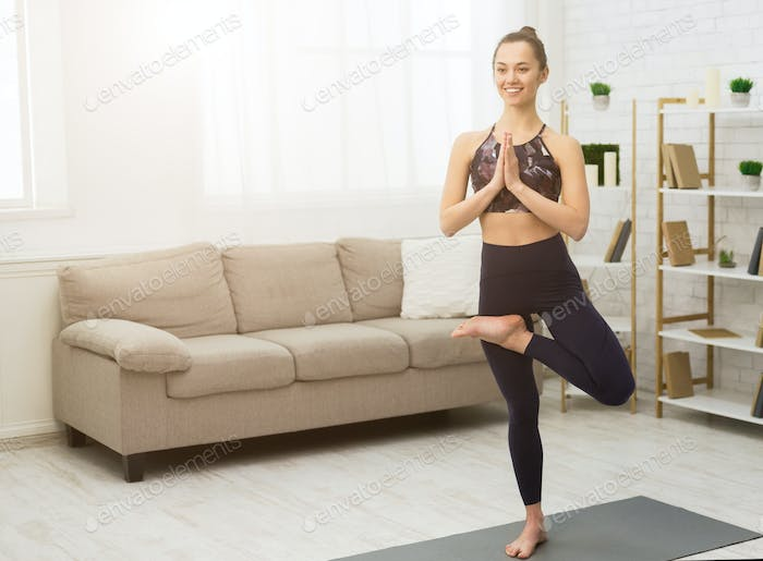 Slim woman practicing yoga in tree pose at home