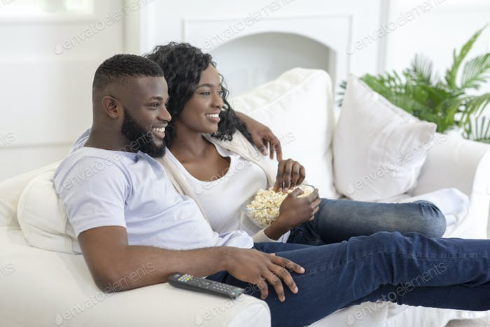 African american couple watching tv, sitting with popcorn at home