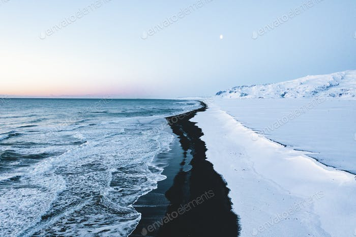 Overhead Aerial Shot of Beautiful Black Beach in Iceland in Winter with Snow