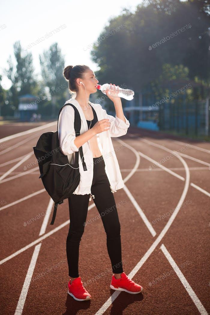 Mädchen im sportlichen Top und Legging mit Rucksack auf Schulter trinken reines Wasser auf der Rennstrecke des Stadions