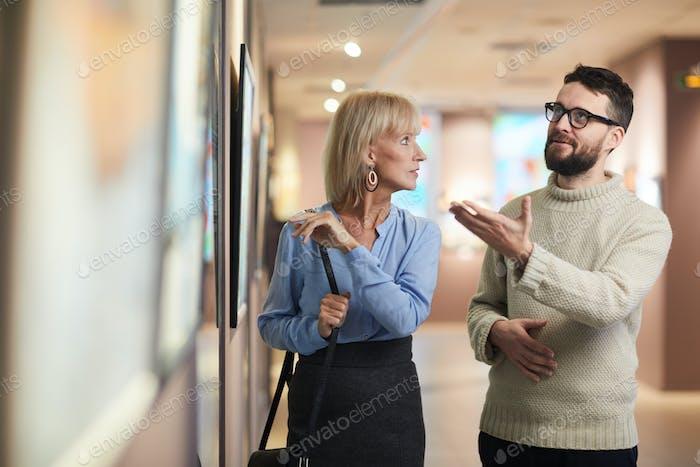 People Discussing Paintings in Art Gallery