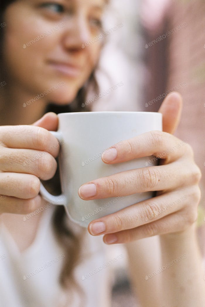 Close up of a woman holding a teacup.