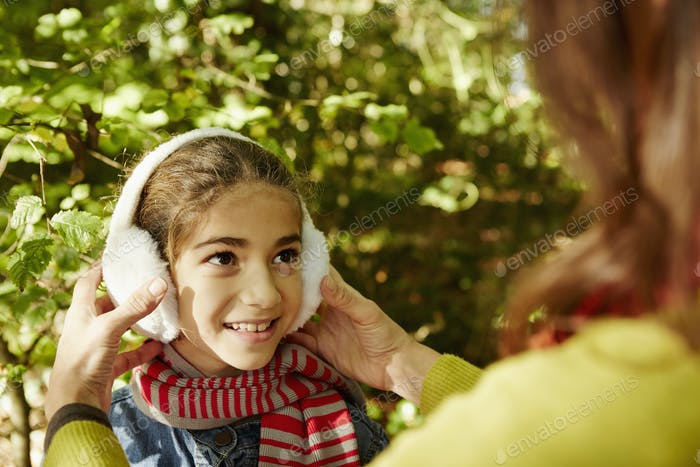 A child wearing warm earmuffs smiling at an adult.